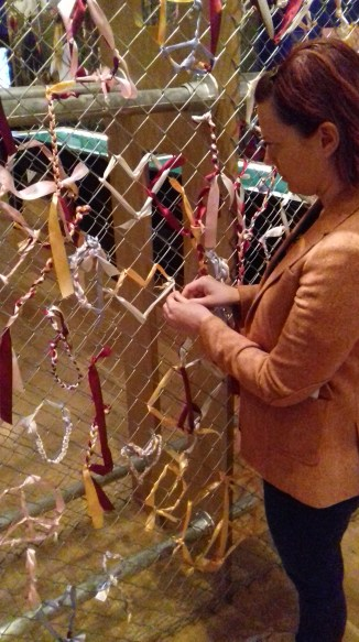 Visitors can tie ribbons to a chain link fence, emulating the Greenham Common protests.
