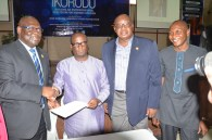 Hon. Benson with the officials after signing the document
