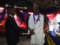 UEC CEO Otunba Saheed Ibikunle presenting presenting certificate to a graduand