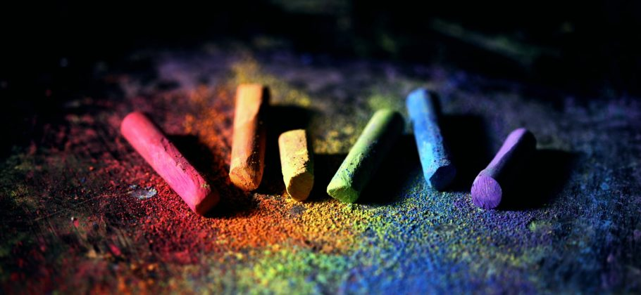 Coloured pieces chalks on a dark background. The colours represent those of the LGBTQ flag: red, orange, yellow, green, blue, purple