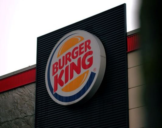 A Photo of the burger king logo on a shop.