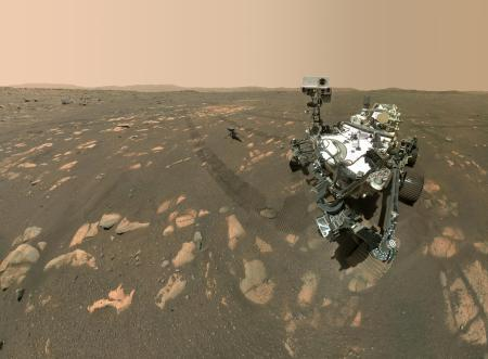 Photograph of the Perseverance Mars Rover in the foregound and the Ingenuity helicopter in the background. The sky is a reddish colour. The surface of Mars shows treadmarks from the Rover