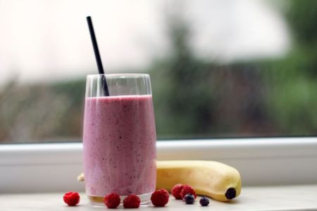 A berry smoothie with a banana and some berries next to it