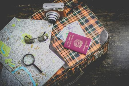 Birds eye view photo of a checked suitcase, with a map, camera and passport on tope