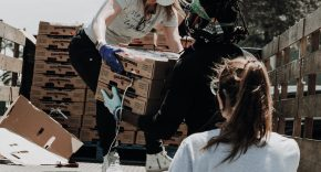 An image of three women passing cardboard boxes of a truck