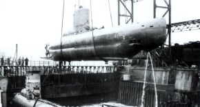 Black and white image of a WW2 Germany U-boat being suspended in the air as it is lifted from the ocean