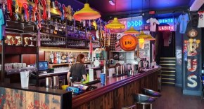 A bar covered in Americana with a bar made in the middle preparing drinks