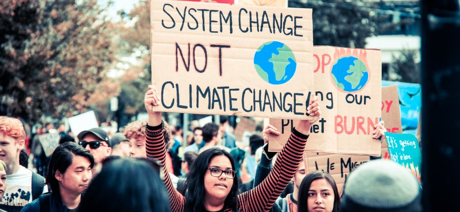Photo showing over 100,000 marching in Vancouver in solidarity with the youth of the world in the September 27 Climate Strike. Sign reads 'System Change Not Climate Change'