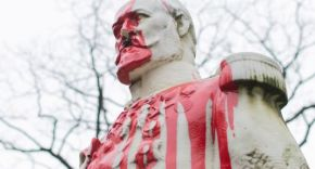 A white statue of a colonial leader is covered in red paint