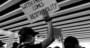 A black and white photo of a protest with a man holding up a sign saying 'With Privilege comes Responsibility'