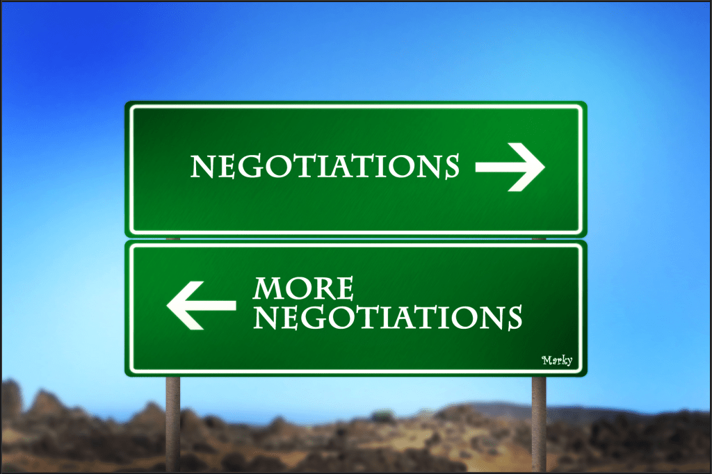 Green road sign with arrows and text that reads negotiations and more negotiations