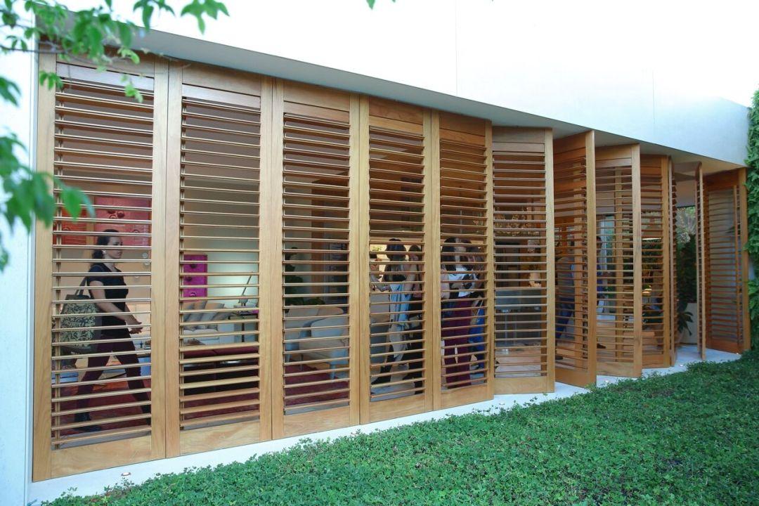 Brises pivotantes em madeira circundam a casa, deixam a paisagem e a luz natural entrarem na medida certa. Paola Ribeiro
