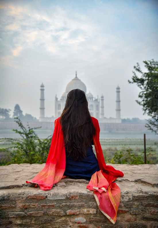 woman sitting on brickwall looking at taj mahal