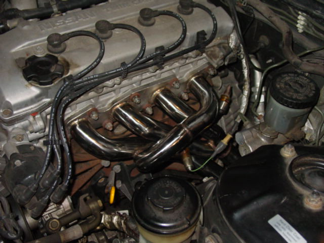 Once you finish comparing the old with the new, carefully slide the header in from the top. It will be a tight fit, but with some effort, you will get it in. Slide on a new gasket, the header, and reinstall all of the manifold bolts.