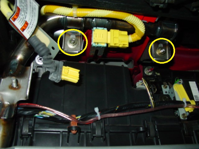 With the cover out of the way, disconnect the yellow air bag harness plug. Also, remove the two nuts located on either side of the yellow plug.