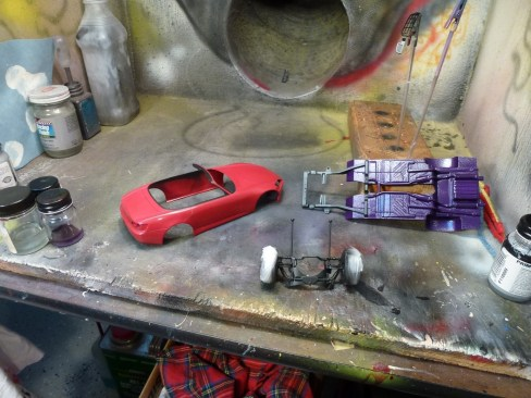 The wheels were glued in place. Masking was required to freshen the paint on the k-member.