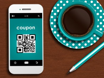 mobile phone with discount coupon, cup of coffee and pencil lyin