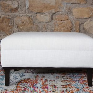 custom ottoman with white linen fabric and dark legs from Impressive Windows and Interiors in Hastings MN