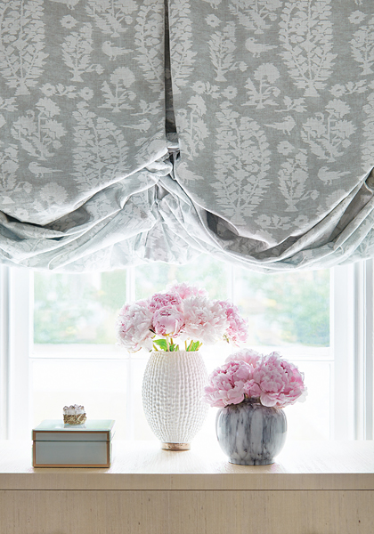 Gray pattern fabric balloon valance on a kitchen window with white trim