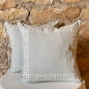 light gray cotton pillow with white embroidered greek key design around perimeter from Impressive Windows & Interiors in Hastings MN