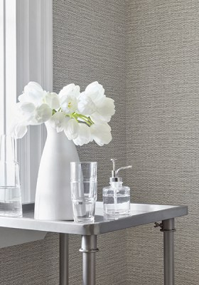 Woven wallcovering in a taupe color by Thibaut- brushed nickel side table with floral and misc bathroom accessories- Impressive Windows and Interiors - Hastings, MN