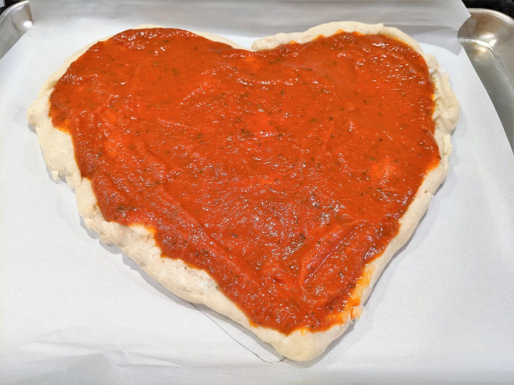 PIzza sauce on the heart shaped dough