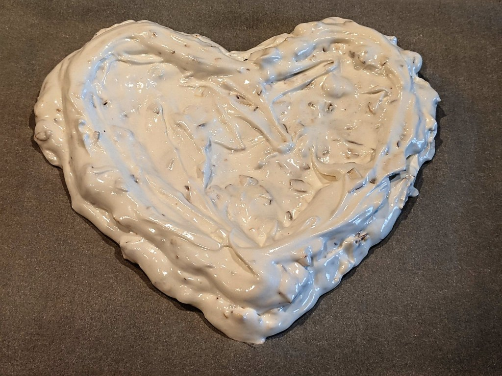 Fill heart shape with meringue, creating a shallow well for the cherry mixture.