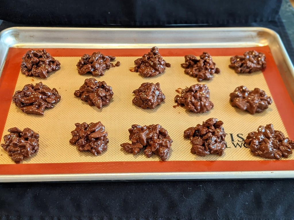 Silicon mat lined baking sheet with clusters dropped in even rows.