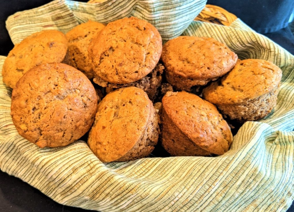 Muffins in basket lined with a green cloth napkin.