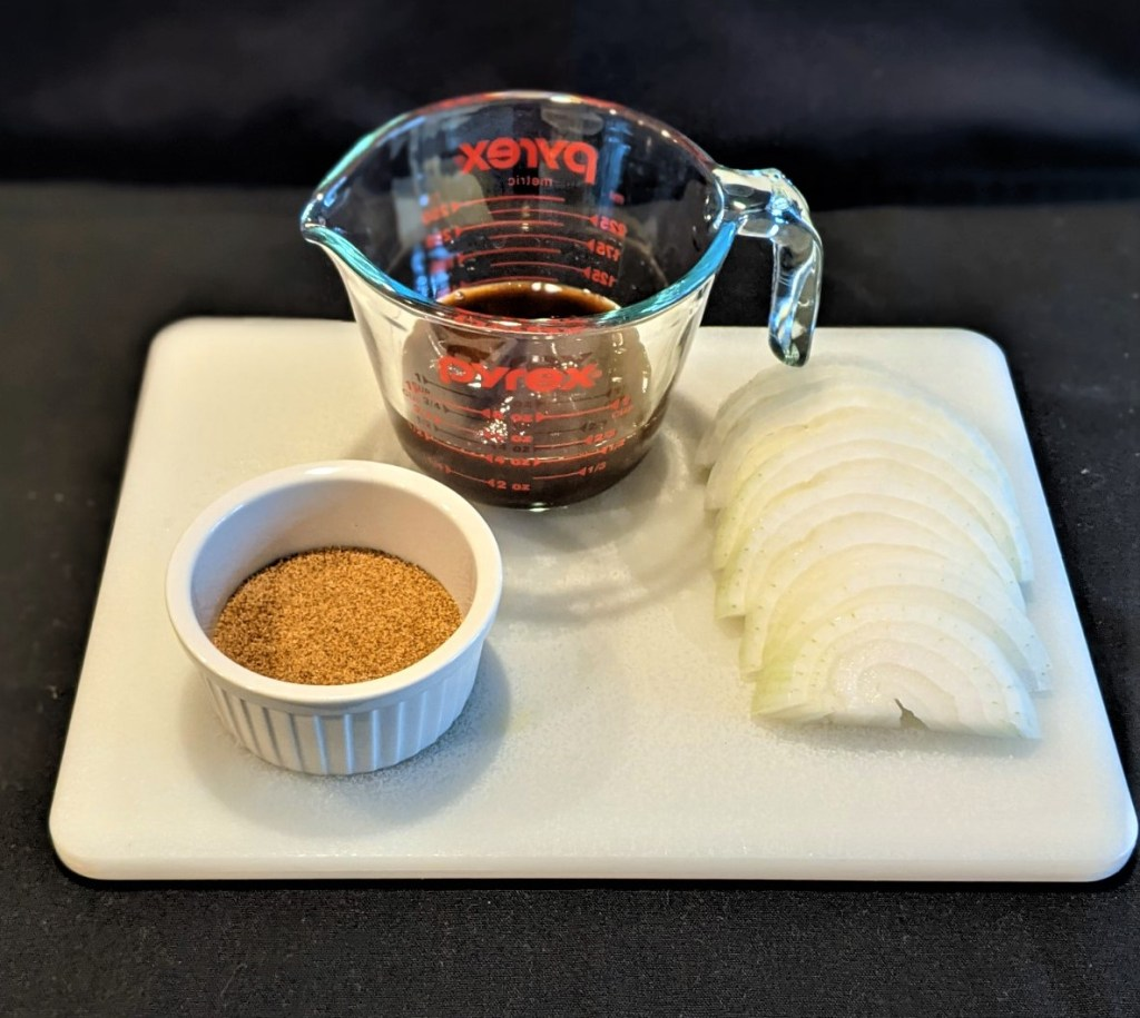 barbeque sauce in measuring cup, spice in a ramekin, and sliced onion