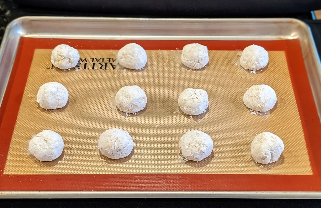 Batter balls coated in sugar on a baking pan