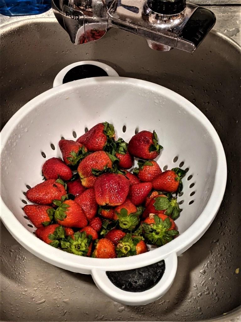 Strawberries in colander in a sink