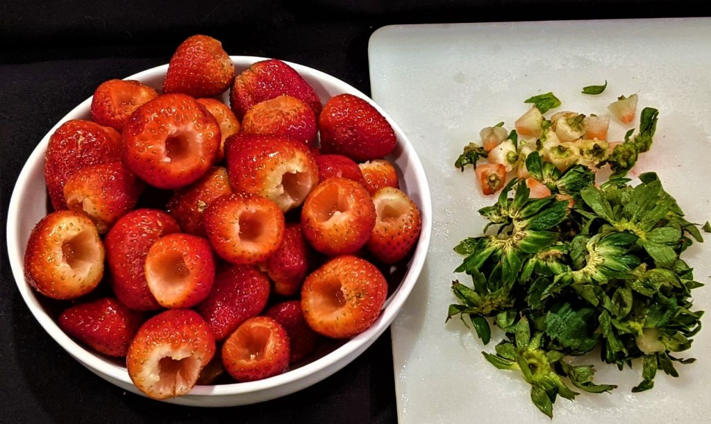 Bowl of strawberries and cutting board with stems and hulls.