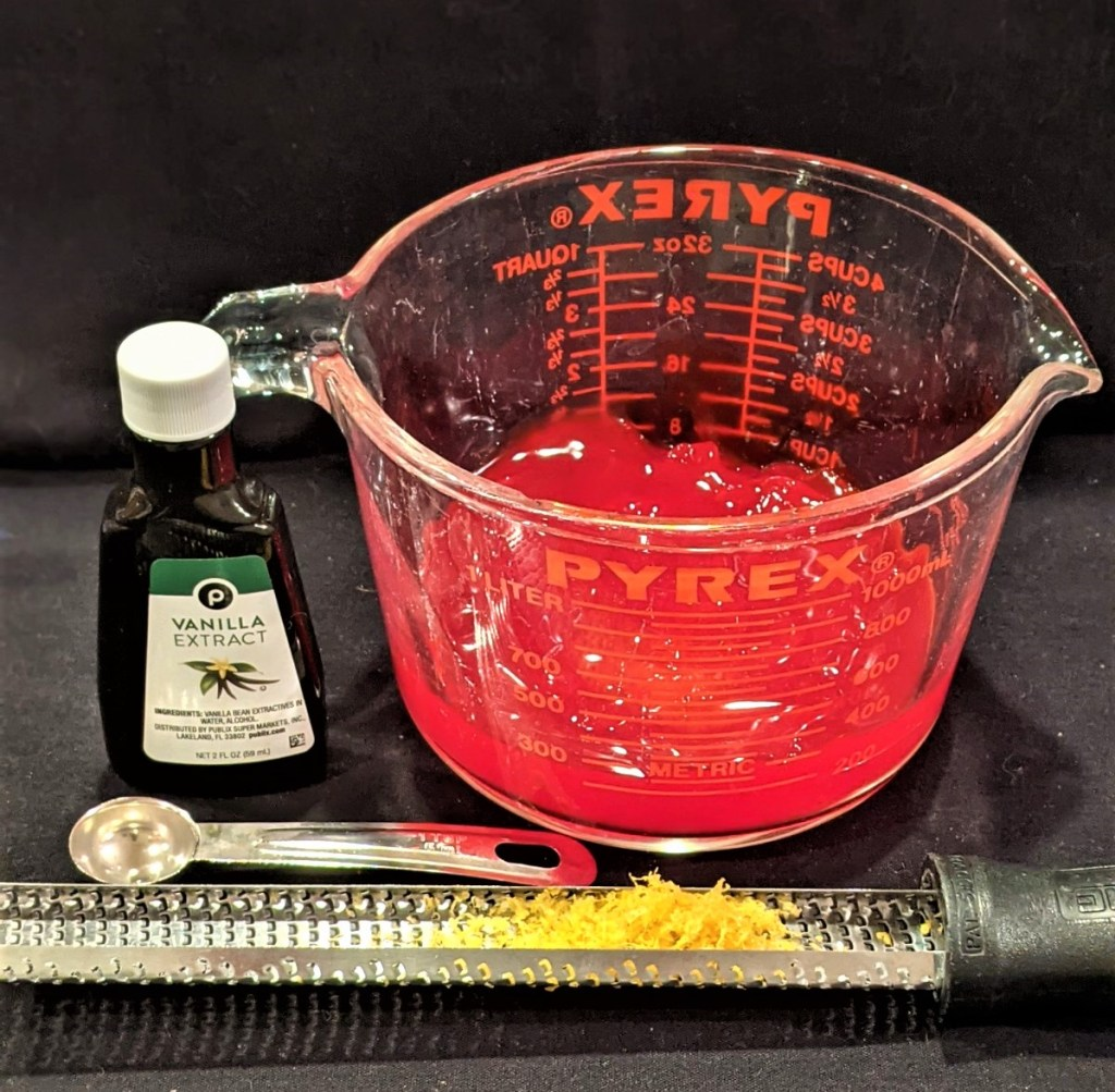 Vanilla extract, strawberry glaze in pyrex measuring cup and lemon zest on a zester/grater.