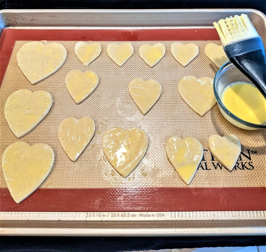 Cut out hearts coated with egg yolk mixture on baking pan