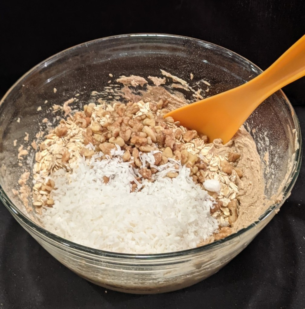 Spoon stirring in oatmeal, coconut and walnuts