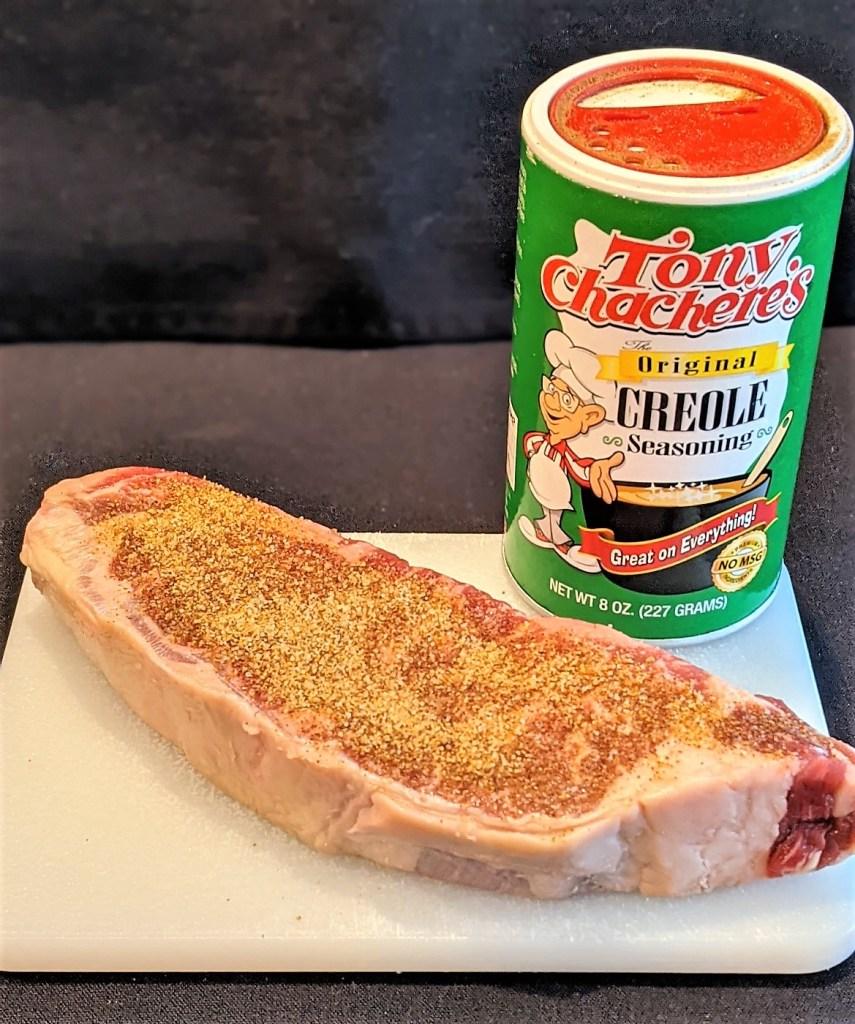 seasoned raw steak and Creole seasoning container