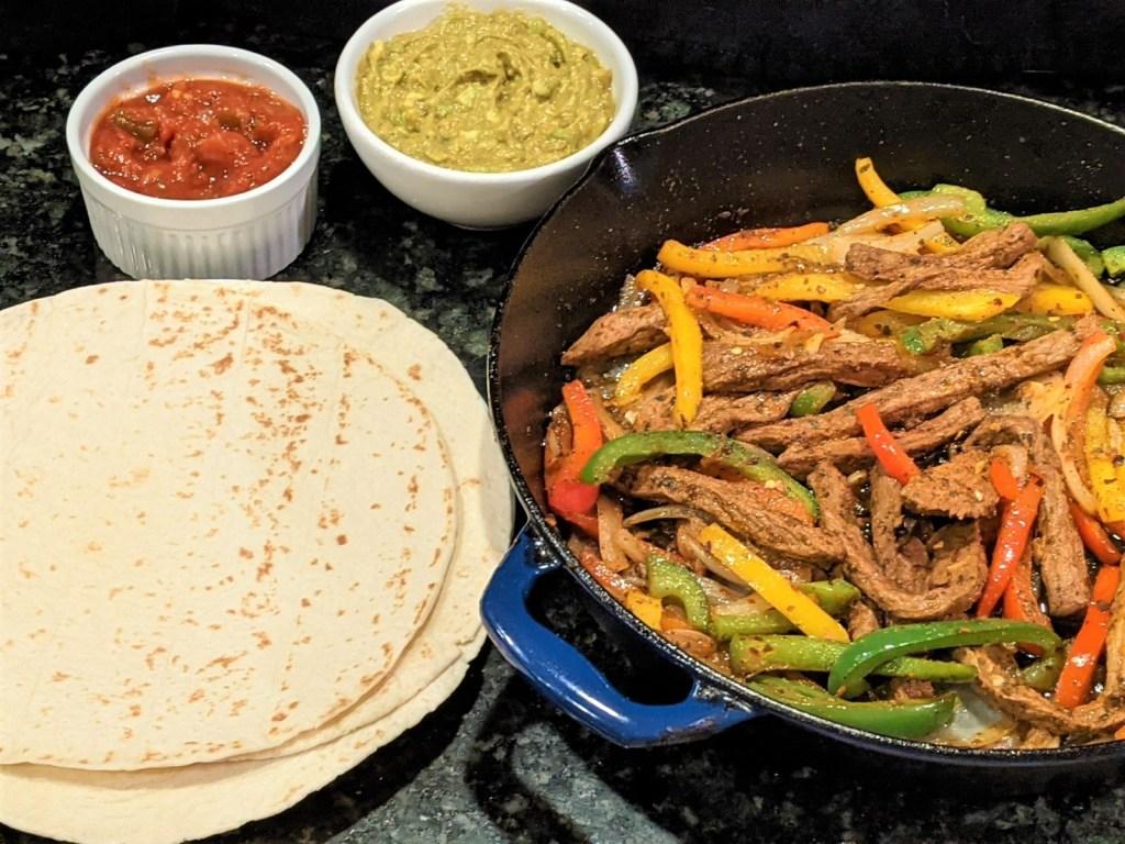 Steak fajitas with guac and salsa dips