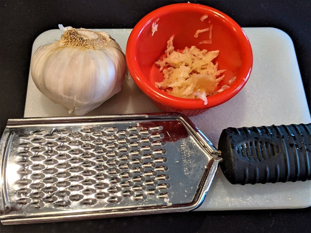 garlic clove, grated garlic in bowl, and side grater on a cutting board