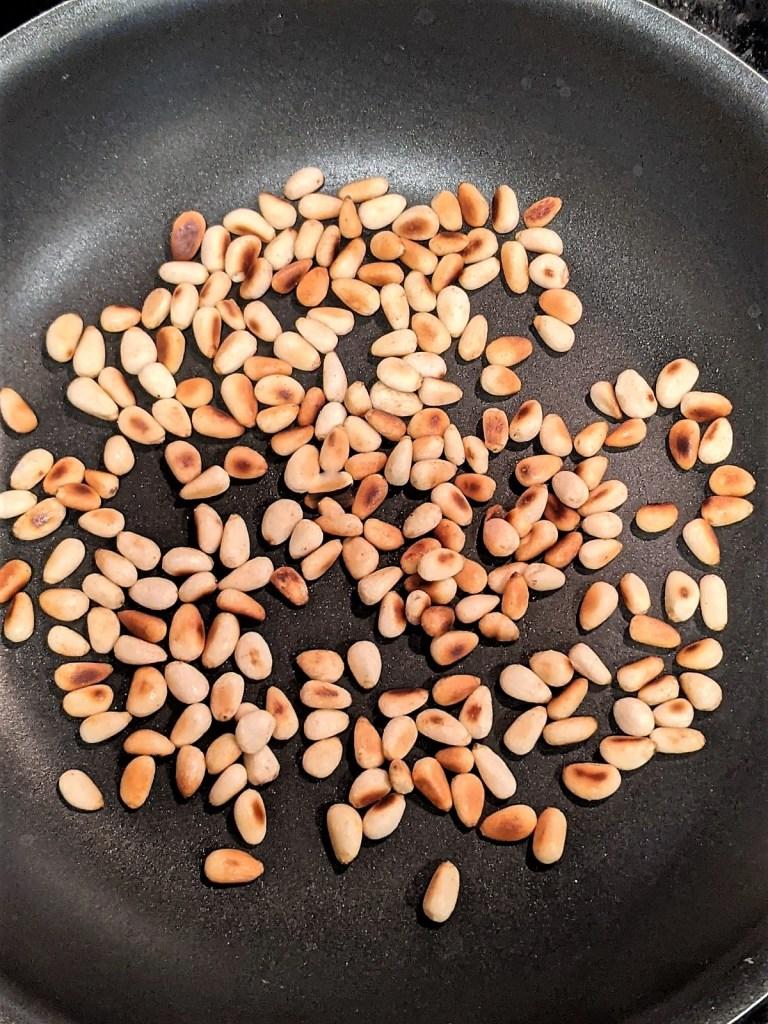 Browned pine nuts in frying pan