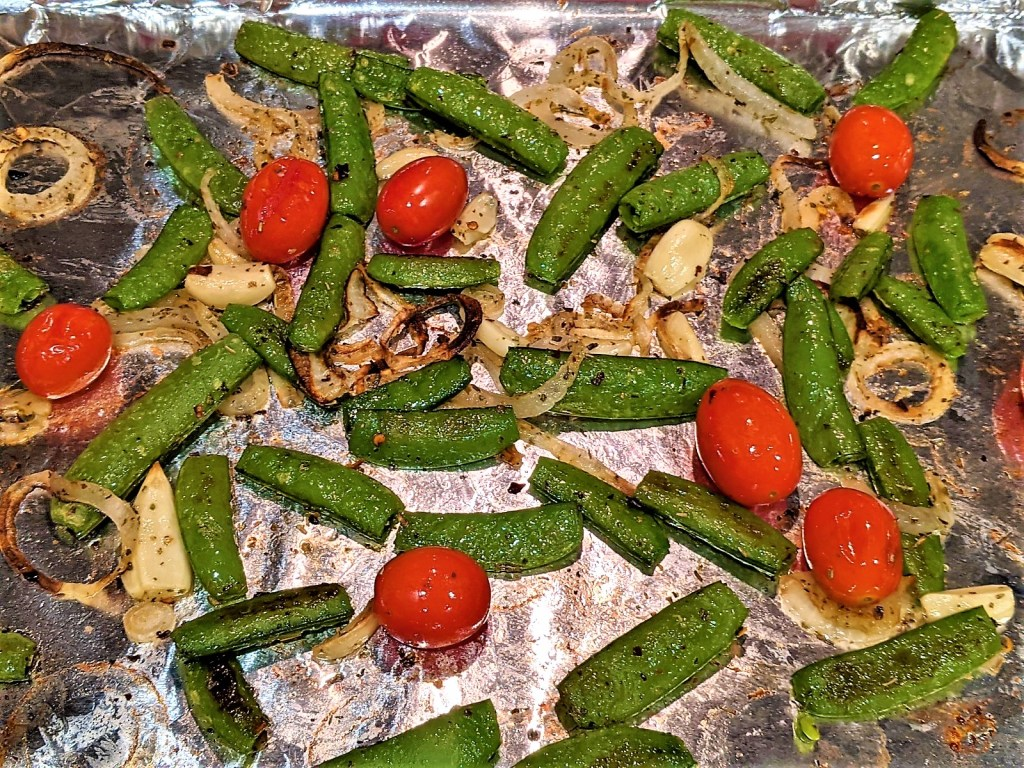 Browned veggies with tomatoes on the foil covered pan