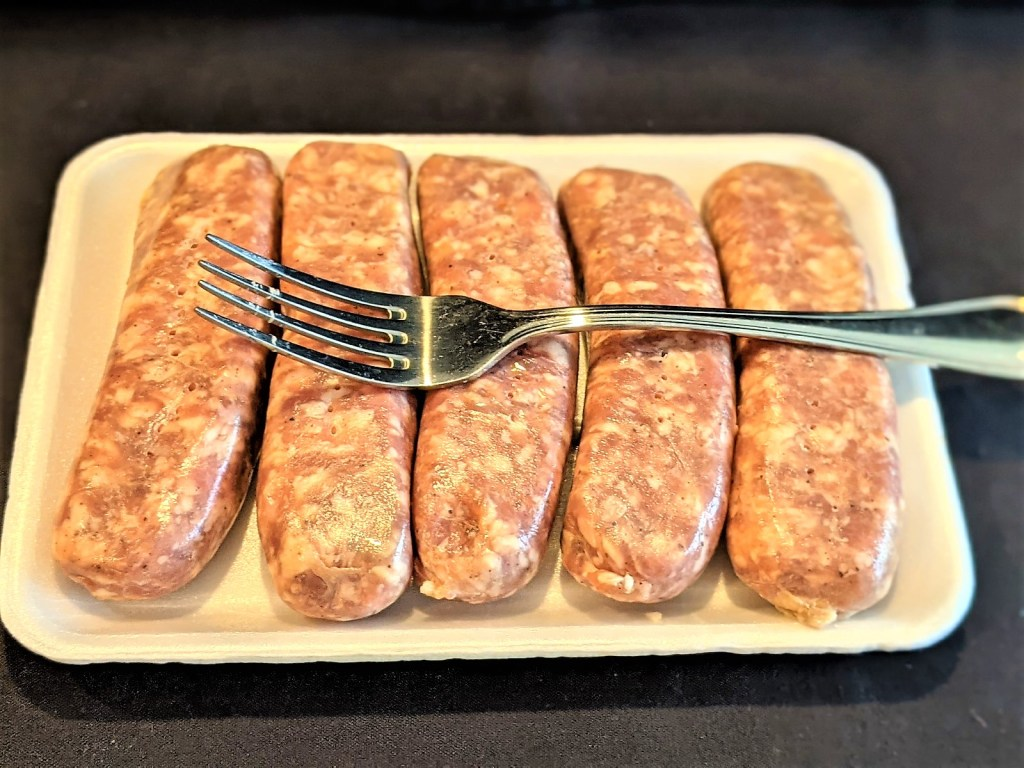 raw brats and a fork