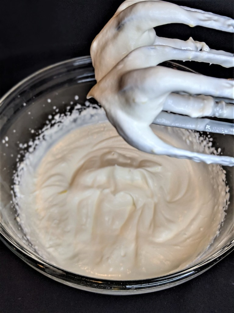 Whipped cream in mixing bowl with mixer