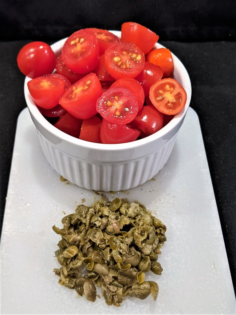 tomatoes and capers on cutting board
