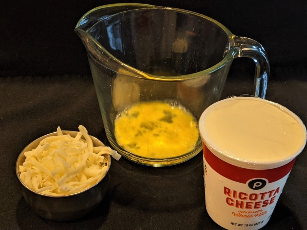 cheese, egg in measuring cup and container of ricotta