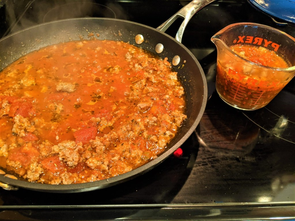 skillet with sauce and measuring cup with sauce