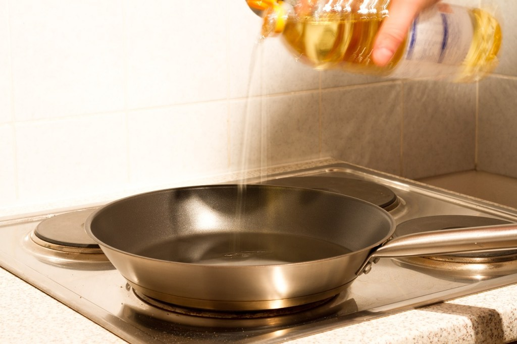Pan with oil being added from bottle