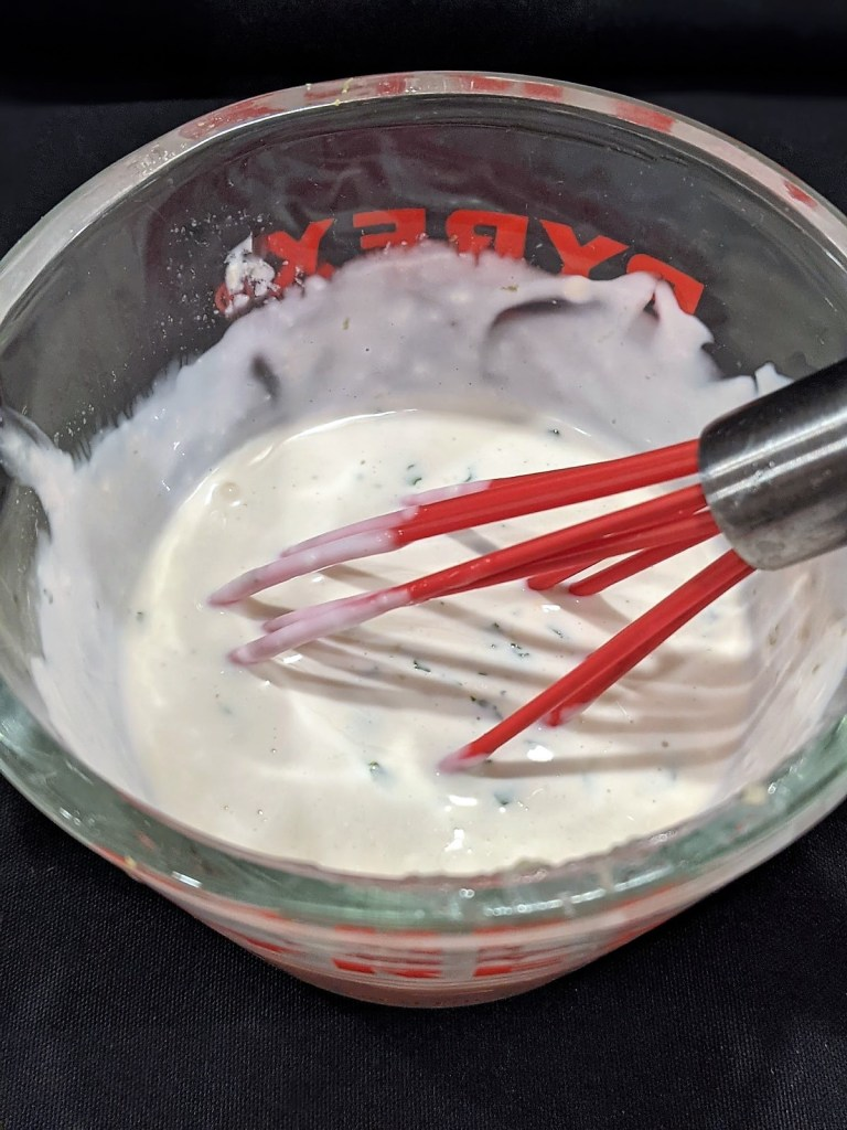 dressing in measuring cup with a whisk