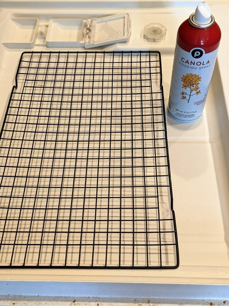 Baking rack on the dishwasher door with non-stick spray can