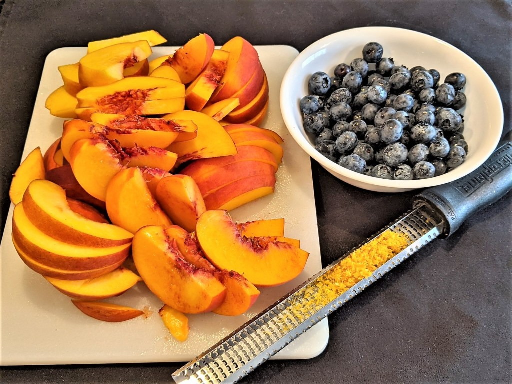 Peach slices, bowl of berries and zester with lemon